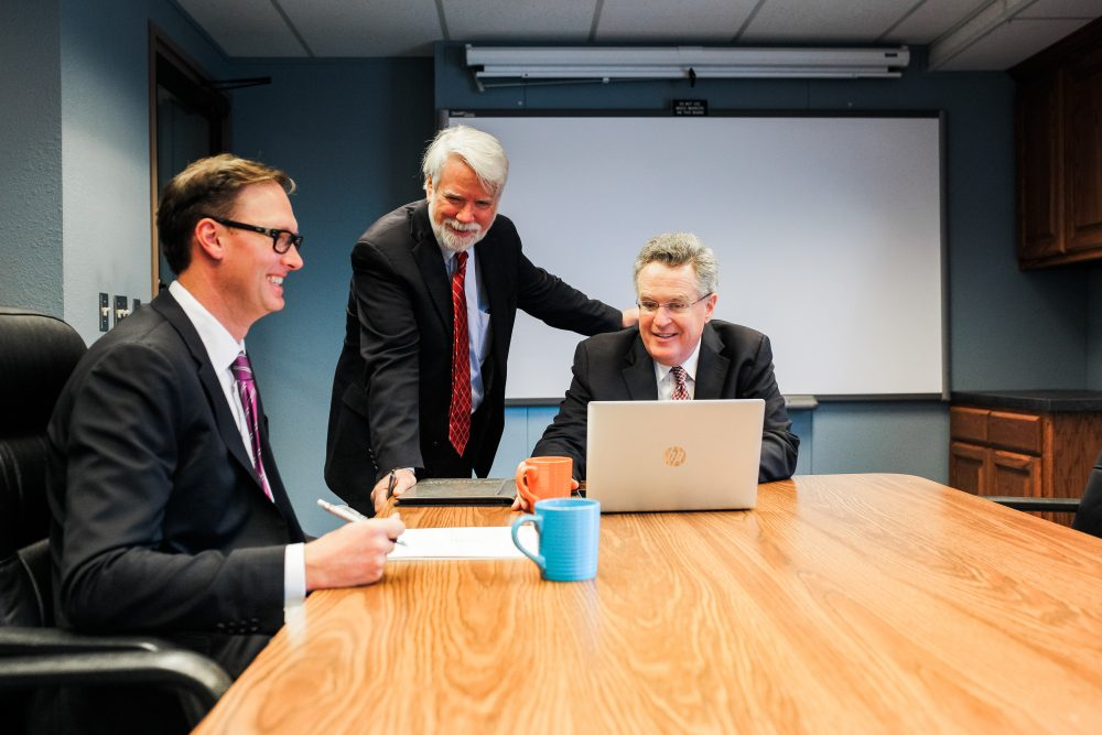 Three lawyers in an meeting discussing a free case assessment